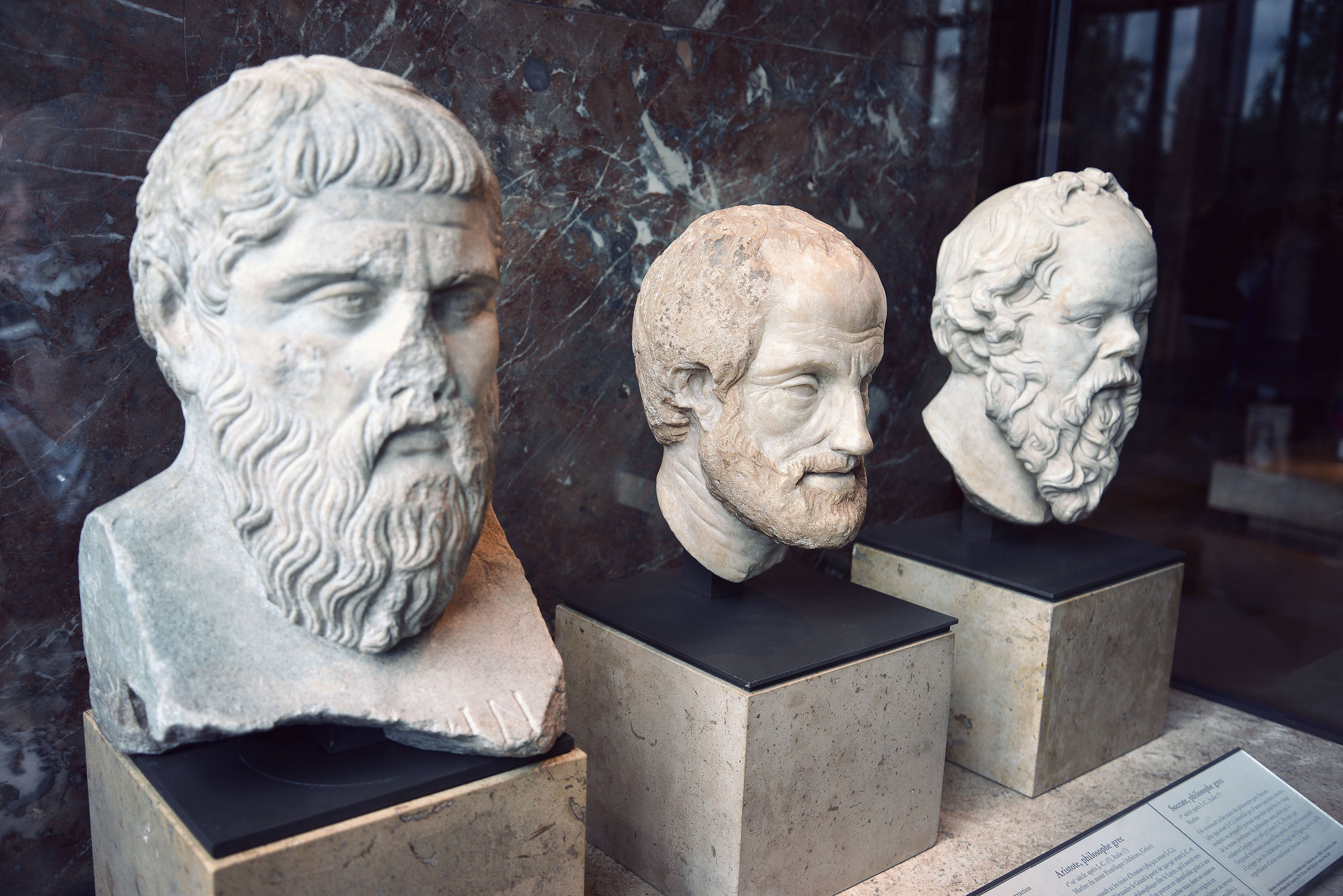 Busts of ancient Greek philosophers Plato, Aristotle, and Socrates.